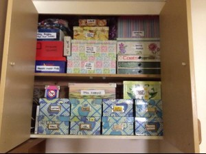Covering boxes with wrapping paper for cheap but effective storage.