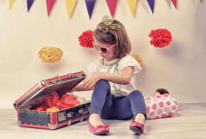 little girl playing with a little retro suitcase